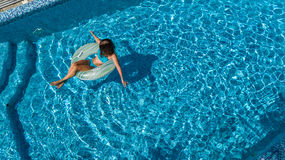 Aerial view of beautiful girl in swimming pool from above, swim on inflatable ring donut in water on family vacation. Aerial view of beautiful girl in swimming Stock Photo