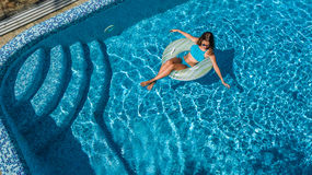 Aerial view of beautiful girl in swimming pool from above, swim on inflatable ring donut in water on family vacation. Aerial view of beautiful girl in swimming Stock Photos