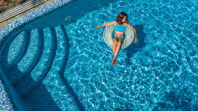 Aerial view of beautiful girl in swimming pool from above, swim on inflatable ring donut in water on family vacation. Aerial view of beautiful girl in swimming Stock Images