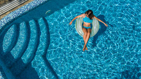 Aerial view of beautiful girl in swimming pool from above, swim on inflatable ring donut in water on family vacation. Aerial view of beautiful girl in swimming Stock Image