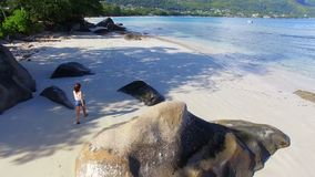 Aerial view of a beautiful girl walking down the Beau Vallon Beach 1, Seychelles. Drone Shot Of A Beautiful Girl Walking Down The Beau Vallon Beach, Mahe Island stock video