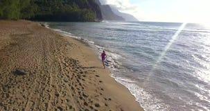 Aerial View of Girl Running on Kauai Island, Hawaii. Aerial view of the beautiful girl walking down the Na Pali coast on Kauai island, Hawaii stock video