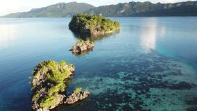 Aerial view of Beautiful Islands and calm water in Raja Ampat. Beautiful limestone islands, surrounded by calm waters and coral reefs, are found in Raja Ampat stock footage