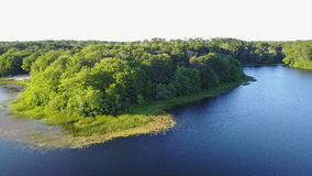 Aerial View of Beautiful Lake on Cape Cod During Summer. Aerial view of the peaceful, summer scenery in a freshwater lake on Cape Cod, Massachusetts. This stock footage