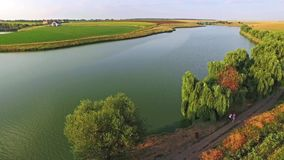 Aerial view of a beautiful landscape with a large river passing through green fields on a sunny day stock video