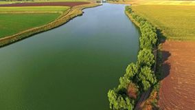 Aerial view of a beautiful landscape with a large river passing through green fields on a sunny day stock video footage