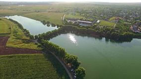 Aerial view of a beautiful landscape with a large river passing through green fields on a sunny day with a view of a small town stock video