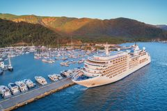 Aerial view of beautiful large white ship at sunset. Cruise ship at harbor. Aerial view of beautiful large white ship at sunset. Colorful landscape with boats in Stock Images