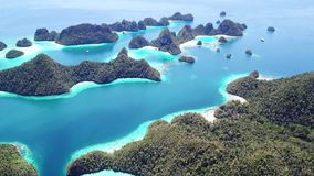 Aerial View of Beautiful Limestone Islands in Raja Ampat. Limestone islands rise from a gorgeous, tropical lagoon in Wayag, Raja Ampat, Indonesia. This unique stock video footage