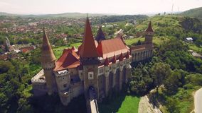 Aerial view of beautiful medieval castle on sunny day with beautiful green fields and hills stock footage