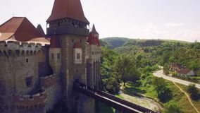 Aerial view of beautiful medieval castle on sunny summer day with beautiful green fields and hills stock video footage