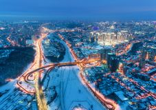 Aerial view of beautiful modern city at cold night in winter. Top view of traffic on roads, buildings, snowy streets with illumination. Skyline. Cityscape from stock image