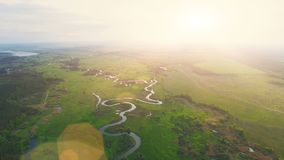 Aerial View: Beautiful river landscape in sunset. 4K Aerial View Drone Footage Flight: 180 degree high shooting of Beautiful River and Green Meadows in sunset stock footage