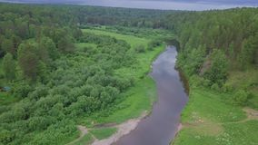 Aerial view of beautiful Russian river located between green meadow and mixed forest against cloudy sky in summer day stock video