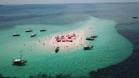 Aerial view of beautiful sand tropical island. With white sand beach and tourists. White sand island. Seascape: ocean and beautiful beach paradise. Zanzibar stock video