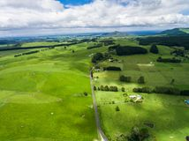 Aerial view sheep farm hill, Rotorua, New Zealand. Aerial view of beautiful sheep farm meadows of green grass on rolling hills in Rotorua, New Zealand North Stock Images