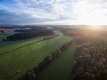 Aerial view of a beautiful sunset over rural landscape with forests and green fields Royalty Free Stock Image