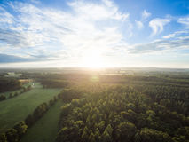 Aerial view of a beautiful sunset over rural landscape with forests and green fields Stock Photography