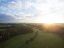 Aerial view of a beautiful sunset over rural landscape with forests and green fields Stock Images