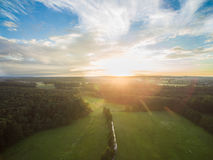 Aerial view of a beautiful sunset over rural landscape with forests and green fields Stock Photo