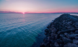 Aerial view of beautiful sunset over water and breakwater. Royalty Free Stock Image