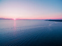 Aerial view of beautiful sunset over water with skyscrapers silh Stock Photos