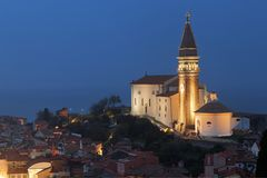 Piran, Istria, Slovenia. Aerial view of beautiful town Piran in Istria, Slovenia, at dusk. Church of Saint George with its bell tower illuminated on the right stock photo