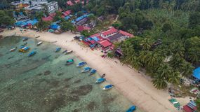 Aerial view of a beautiful tropical beach with some resorts and boats in the sunrise. Perhentian Island, Malaysia. Aerial view of a beautiful tropical beach with stock photo