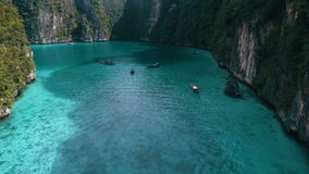 Aerial view of beautiful tropical turquoise water with boats. Aerial drone view of iconic tropical turquoise water Pileh Lagoon surrounded by limestone cliffs stock video footage