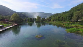 Aerial view of beautiful Una river in Bosnia with smoke rising in background stock video