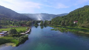 Aerial view of beautiful Una river in Bosnia with smoke rising in the background stock footage