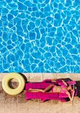 Beautiful young woman laying on sunbed at poolside. Aerial view of beautiful young woman in bikini laying on pink sunbed at poolside Royalty Free Stock Image