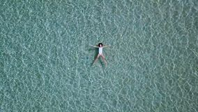 Aerial view. Beautiful young woman in white bikini floating on water surface in crystal clear turquoise color ocean stock video