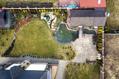 Aerial view of beautifully landscaped recreation house cottage complex with pond in ecological area on bright sunny day. Modern stock photo
