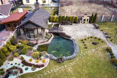 Aerial view of beautifully landscaped recreation house cottage complex with pond in ecological area on bright sunny day. Modern. Architecture, riches and luxury royalty free stock images