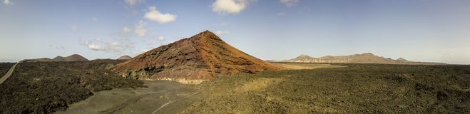 Aerial view of the Bermeja mountain of an intense red color, surrounded by lava fields, Lanzarote, Canary Islands, Spain. Aerial view of the Bermeja mountain of royalty free stock photos