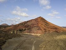 Aerial view of the Bermeja mountain of an intense red color, surrounded by lava fields, Lanzarote, Canary Islands, Spain. Aerial view of the Bermeja mountain of royalty free stock image