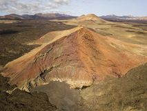 Aerial view of the Bermeja mountain of an intense red color, surrounded by lava fields, Lanzarote, Canary Islands, Spain. Aerial view of the Bermeja mountain of stock images
