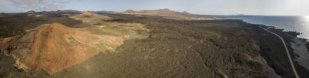 Aerial view of the Bermeja mountain of an intense red color, surrounded by lava fields, Lanzarote, Canary Islands, Spain. Aerial view of the Bermeja mountain of stock photos