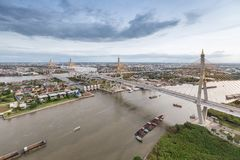 Aerial view of Bhumibol suspension bridge cross over Chao Phraya. River in Bangkok city with car on the bridge at sunset sky and clouds in Bangkok Thailand royalty free stock photography