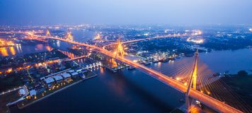 Aerial view of Bhumibol Suspension Bridges and highways interchange over the Chao Phraya River at dusk. Samut Prakan, Thailand. Soft focus, aerial view of royalty free stock photos