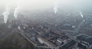 Aerial view of big factory in China. Air pollution by smoke coming out of chimneys.
