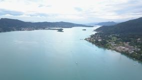 Aerial view of a big lake in mountains. Boat moves on the lake. Klagenfurt Carinthia Austria. stock footage