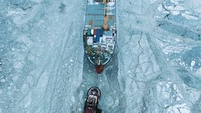 Aerial view. The big ship sails through the sea ice in the winter, close-up stock images