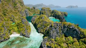 Aerial view of big and small lagoon on Miniloc Island. El-Nido, Palawan. Philippines. Limestone rock formation covered. With plants surrounded by blue blue stock footage