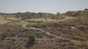 Aerial shot of a man riding a mountain bike on rural landscape in a sunny day. Aerial view of a biker riding a mountain bike on a rural landscape stock footage