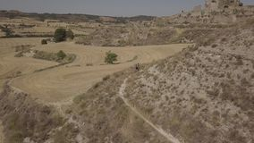 Man riding mountain bike on rural landscape in a sunny day. Aerial view of a biker riding a mountain bike on a rural landscape stock footage