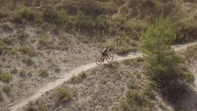 Mountain biker riding up a trail in a rural landscape. Aerial view of a biker riding a mountain bike on a rural landscape stock footage