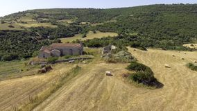 Aerial view, bird eye of the ancient ruin church in the middle of fields with hay bales