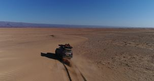 Aerial view of black car driving in sahara. Cinematic drone shot flying over desert stock video